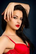 woman in beautiful red lingerie on dark background - stock photo