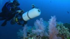 Scuba diver swimming with scooter over coral garden Stock Footage