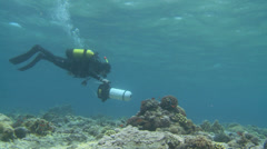Scuba diver swimming with scooter over the coral reef Stock Footage