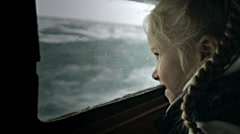 Girl looks through the ship window at waves Stock Footage