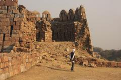 local guard walking around tughlaqabad fort, new delhi - stock photo