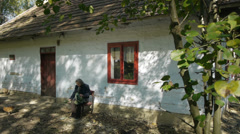 Old person in front of a cottage Stock Footage