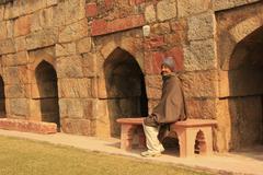 indian man sitting on a bench at mausoleum of ghiyath al-din tughluq, tughlaq - stock photo