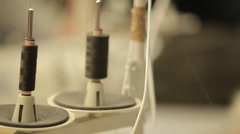 Sewing machine's cotton reels   rack focusing to man working Stock Footage