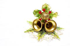 two gold bells and bauble on plastic leaf sprig - stock photo