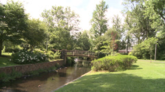 Creek and bridge in sun and shadow Stock Footage