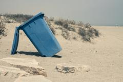 wheelie bin on sandy coast - stock photo