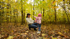 Little Baby is Playing with Mother in Autumn Colorful Forest - stock footage
