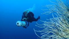 Scuba diver swimming with scooter, along coral reef - two footage Stock Footage
