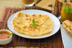 roti canai and teh tarik, very famous drink and food in malaysia - stock photo