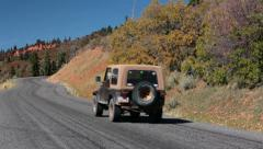 Jeep drives up mountain road autumn colors HD 9956 - stock footage