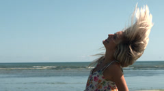 Happy blonde shaking hair on the beach - stock footage