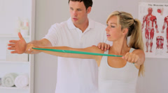 Physiotherapist using a resitance band with his patient Stock Footage