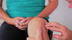Physiotherapist checking his patients knee - stock footage