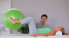 Physiotherapist watching his patient move an exercise ball in between her knees - stock footage