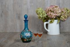 Former decanter with two small glasses with liqueur Stock Photos