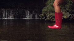 Woman in pink rubber boots running in water Stock Footage