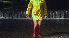 Woman wearing pink rubber boots splashing in water Stock Footage