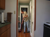 Stock Video Footage of Man Sweeping Apartment