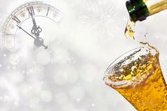 Pouring champagne against holiday lights and clock Stock Photos