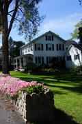 colorful flowers and classic new england home - stock photo