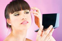 woman checking face skin in mirror - stock photo