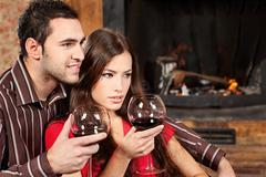 couple enjoying wine near fireplace - stock photo
