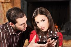 couple drinking wine near fireplace - stock photo