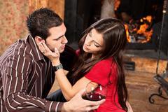 woman caress her man near fireplace - stock photo