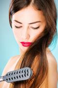 Woman with long hair holding comb Stock Photos