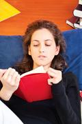 woman reading book at home - stock photo