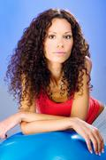 pretty curls hair women on blue pilates ball - stock photo