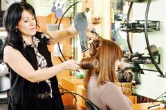 hairdresser drying customer's hair - stock photo