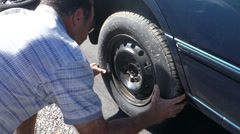 Changing tire on car 1 Stock Footage