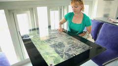 Woman exploring map on touch screen table - stock footage