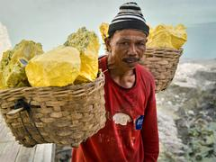 Miner Carrying Baskets of Solid Sulfur at Kawah Ijen Volcano Stock Photos