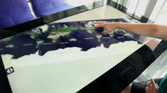 Woman scaling and moving around world map chart on touch display Stock Footage