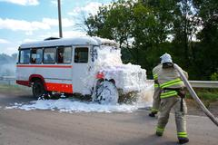 Firefighters extinguish a fire in a burning bus Stock Photos