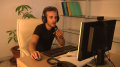 Man with wireless headphones and microphone working on PC with webcam. Stock Footage
