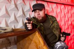 young bearded terrorist with a gun in the stroma of a dilapidated shelter - stock photo