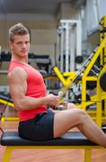 handsome young man working out on gym equipment - stock photo