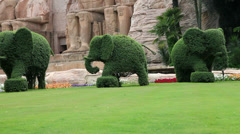 Green park of elephant sculptures from shrubs Stock Footage