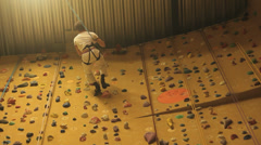 A man climbes in a climbing hall Stock Footage