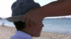 Mother applying suntan lotion to her son Stock Footage