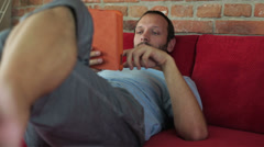 Man using tablet and lying on the sofa Stock Footage