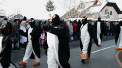 Penguin dressed people are walking past audience Stock Footage