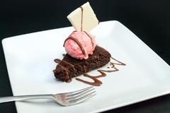 brownie with raspberry icecream, fork on plate - stock photo