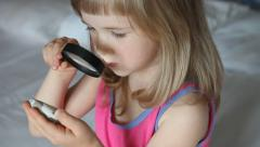 Charming little girl playing with a magnifying glass Stock Footage