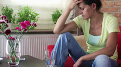 Worried woman sitting on the sofa - stock footage