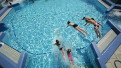 Over the head shot of kids jumping into pool outside by the river - stock footage